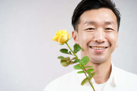 asian man smiling with yellow rose flower