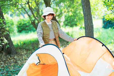 Asian young woman preparing a tent for camping