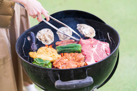 Asian young woman baking ingredients on BBQ Stockfoto