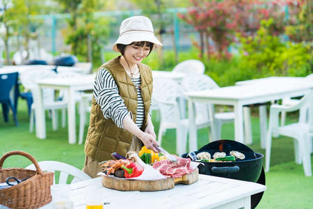 Asian young woman baking ingredients on BBQ Foto de archivo