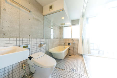 Toilet and bathroom separated by glass wall