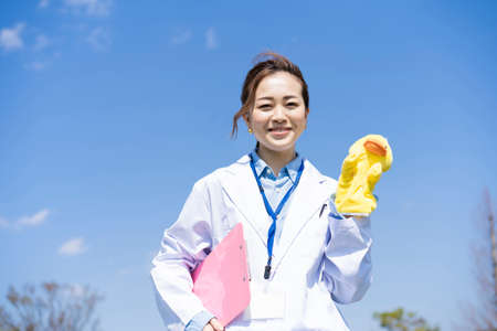 Asian woman in a lab coat and holding a puppet doll outdoors Foto de archivo