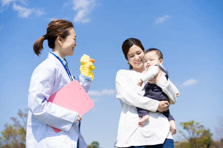 Parent and child talking to a woman in a lab coat and holding a puppet doll on fine day Foto de archivo