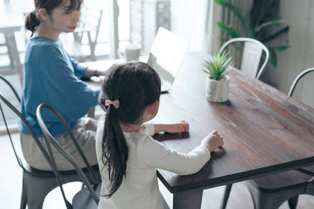 A child talking to a woman teleworking at home Foto de archivo