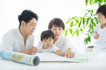 Parents and children studying happy using maps / Parents and children planning trips using maps Standard-Bild