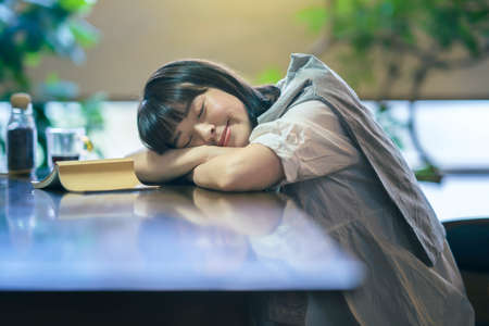 A young woman napping in a moderately bright room with abook and glass of coffee