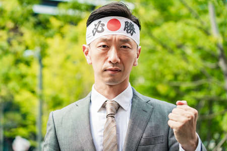 """A man who wraps a """"must win"""" headband and makes a guts pose.The characters written on the headband are in Japanese, and the meaning is """"must win."""""""