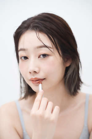 Asian young woman applying lipstick to her lips