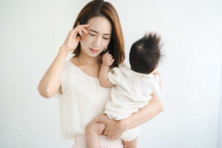 Asian mother holding a baby and looking tired