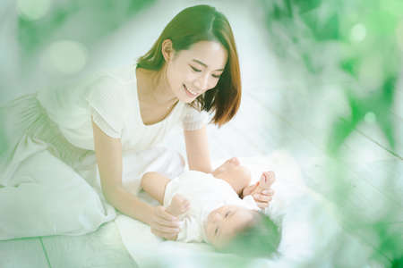 Asian mom and baby playing indoors