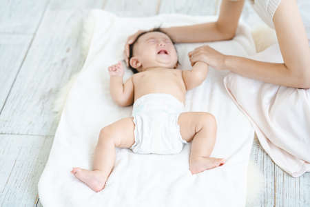 Baby crying in a diaper on the floor Standard-Bild