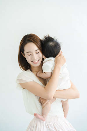 Asian mom holding a baby in the bright room Standard-Bild