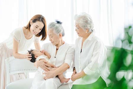 Senior women hugging babies and women watching over