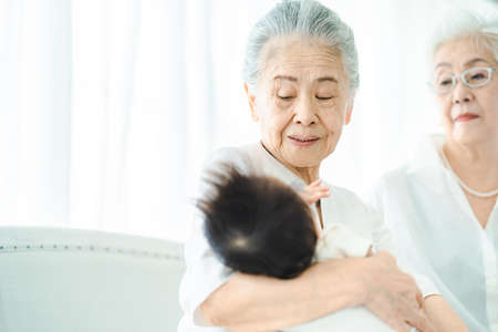Senior women hugging newborn baby in the room Standard-Bild