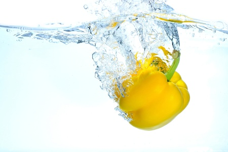 falling water: The paprika which jumps into water Stock Photo