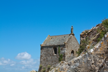 Stone chapel with a saint on the roof - Saint Michel, France