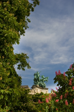 Roof statue of the Grand Palais, framed by blossomed trees