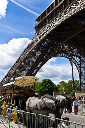 Iconic image at the base of the famous Eiffel Tower with a carriage, waiting for tourists