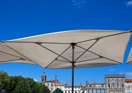 Big white terrace umbrella against blue sky and the buildings of Rochefort, France