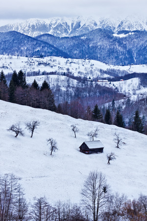 old barn in winter: Piatra Craiului mountain massive, Romania - winter landscape