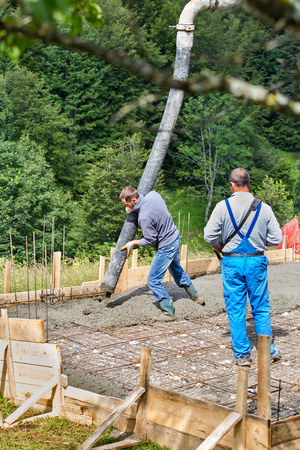 on site: Builders pouring cement on a small construction site