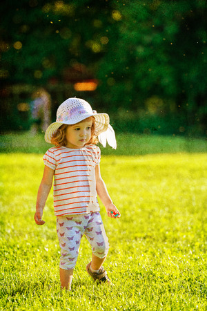 Cute little girl with fancy hat walking in the grass in summer time