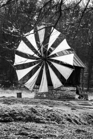 Old traditional windmill in romanian countryside on black and white Stock Photo
