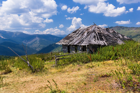 Mountain landscape with a deserted wooden hut Stock Photo