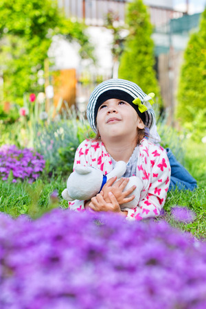 Beautiful child holding a toy bear in her arms, looking up in the flowers garden