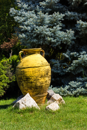 Big yellow painted clay pot as garden decorative element Stock Photo