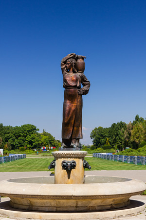 commissioned: BUCHAREST, ROMANIA - AUGUST 15, 2012. The Modura Fountain, containing a bronze statue of the romanian peasant heroine. It was commissioned from sculptor Constantin Baraschi for the opening of Herastrau Park in 1936 Editorial
