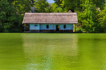 danube delta: Traditional fisherman wooden house near river and covered by trees