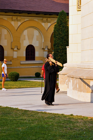 Alba Iulia, Romania - August 26, 2012: Orthodox priest hitting a wooden board calling the people to prayer and service