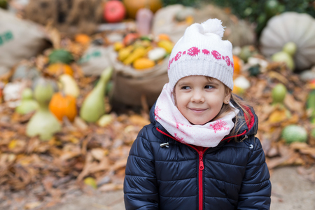 Cute little girl looking on the right side, having a pile of pumpkins in the background
