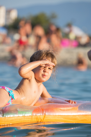 floatable: Cute little girl sitting on a floatable mattress, covering his eyes from the sun