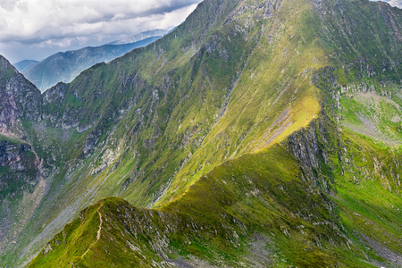 Fagaras mountains in Romanian Carpathians, with a people on the trail at Nerlinger monument