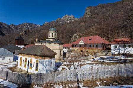 Orthodox monastery Stanisoara in Cozia mountain during sunny winter day