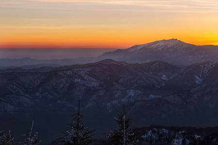 Buila-Vanturarita mountain seen from Cozia mountain at dusk during winter