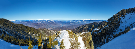 Panoramic view over Olt Valley and Fagaras, the highest mountain range in Romania during winter from Cozia mountains