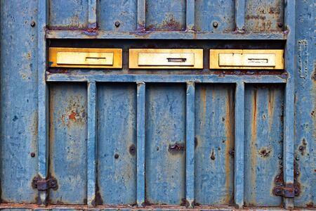 Rusty metallic door with three golden mail boxes