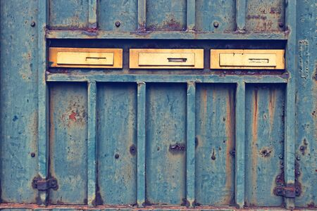 Rusty metallic door with three golden mail boxes with retro filter