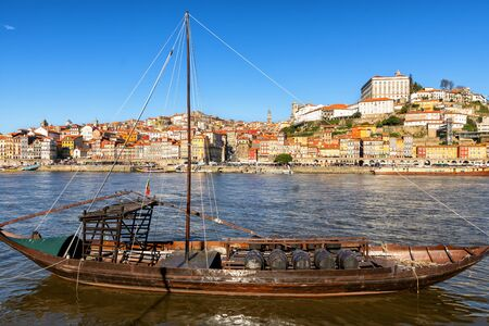 View of Douro River and the city of Porto, large boats with barrels of wine - port, the most famous bridge and boats to transport wine