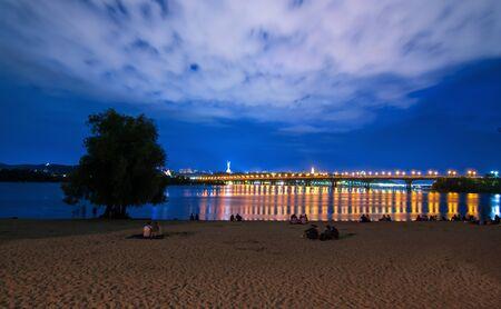 Evening view of Kyiv, night city lights, bridge over the river, panorama of the capital of Ukraine Archivio Fotografico