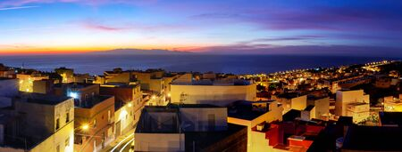 Dawn on Tenerife Island in a small town, colorful houses, sun rising over Gran Canaria