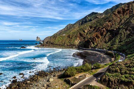 Black volcanic sand beach - Beniho, ocean waves flow smoothly to shore, huge rocky cliffs in the ocean Archivio Fotografico