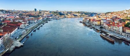 View of the city of Porto from the Eiffel Bridge early in the morning at dawn, small multicolored houses of the Ribeira Quarter Archivio Fotografico