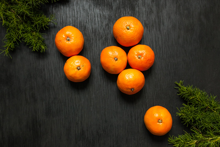 Tangerines on a black background. Lots of fresh fruit - mandarins. High quality photo