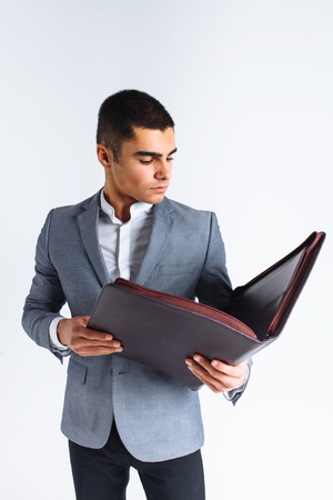 Handsome man with folder man reading a menu, a stylish business guy in suit in Studio on white background isolated Banque d'images
