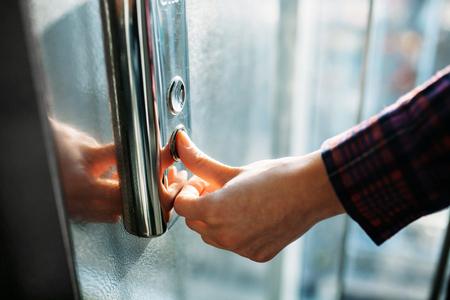 De duim drukt op de liftknop, een hand reikt naar de knop, het meisje wacht op lift, drukknop start, geïsoleerd