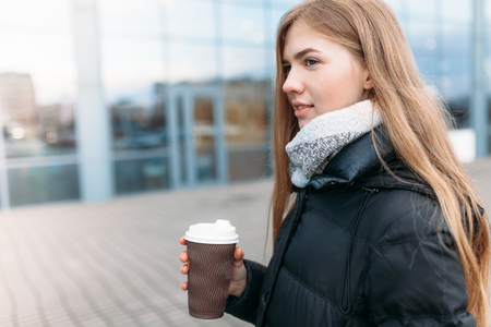 Das Mädchen geht die Straße mit einer Tasse Kaffee, Nahaufnahme, gutes Wetter, Frau in Jacke